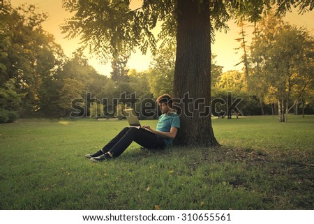 Man sitting in the park under a tree - stock photo