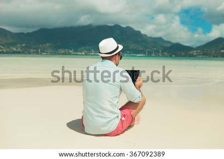 man sitting in the sand with legs crossed while reading from ipad in an exotic place - stock photo
