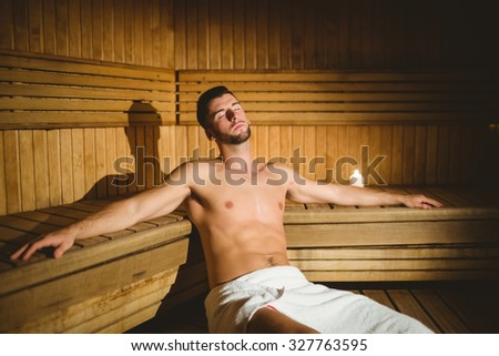 Man sitting inside a sauna at the spa - stock photo
