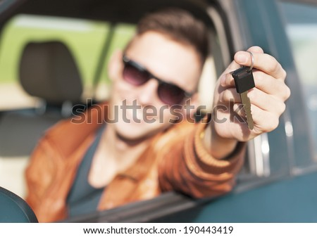 Man sitting inside car and showing keys to new car  - stock photo
