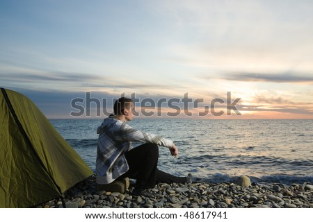 Man sitting near his camp at sunset