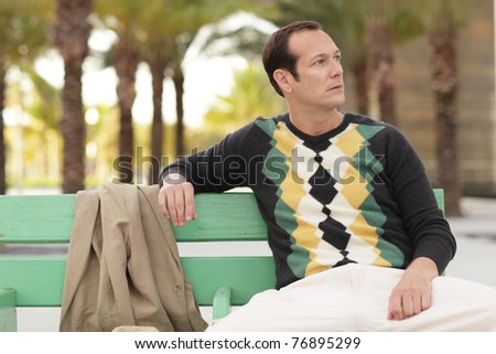 Man sitting on a bench - stock photo