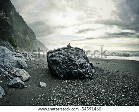 Man sitting on a big rock on a rocky beach watching the ocean. Location: Hualien County, Taiwan - stock photo