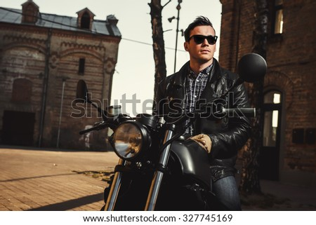 Man sitting on a cafe-racer motorcycle outdoors - stock photo
