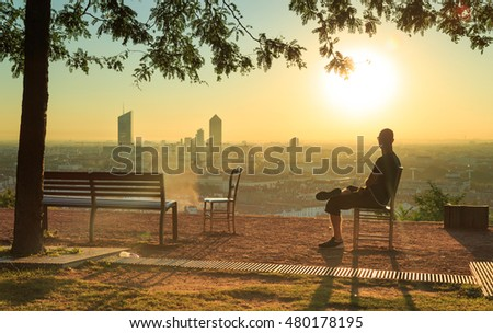 Man sitting on a chair and enjoying the sunrise over the city of Lyon, France.