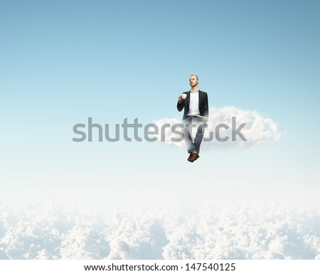 man sitting on a cloud with cup of coffee - stock photo