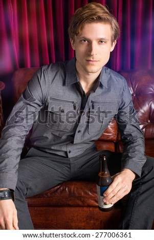Man sitting on a couch in a club with a beer - stock photo