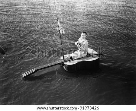 Man sitting on a  guitar sailboat - stock photo