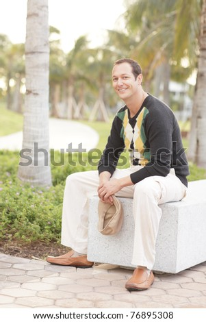 Man sitting on a park bench - stock photo