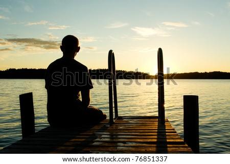 Man sitting on a pier on sunset - stock photo