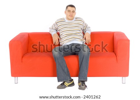 Man sitting on a red couch.  Isolated on white background, in studio. - stock photo