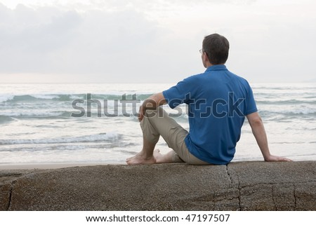 Man sitting on a rock at the sea - stock photo