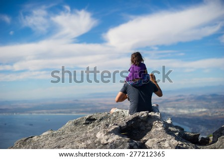 Man sitting on a rock carrying his daughter while they are both overlooking the city. The skies are bright blue and slightly cloudy.