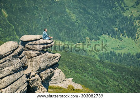 Man sitting on a rock in the lotus position and looking at the sky - stock photo