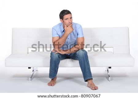 Man sitting on a sofa - stock photo