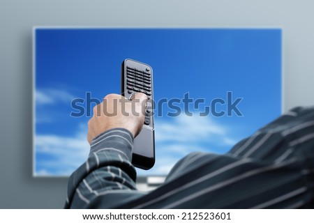 Man sitting on a sofa watching tv holding remote control - stock photo