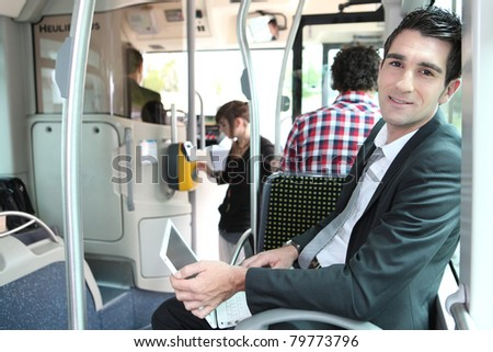 Man sitting on a tram working at a laptop computer - stock photo
