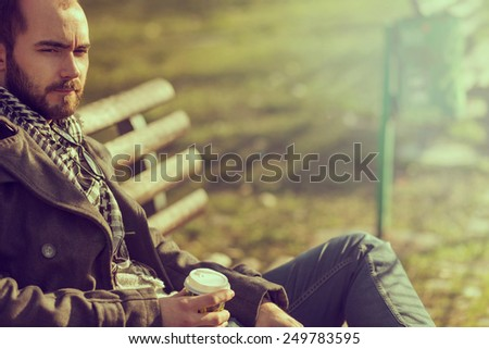 Man sitting on a wooden bench in the park and drinking coffee - stock photo