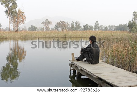 man sitting on a wooden pier