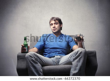 Man sitting on an armchair and holding a remote control and a bottle of beer - stock photo