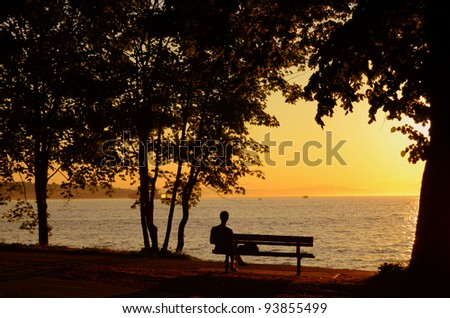 Man Sitting On Bench During A Beautiful Sunset - stock photo