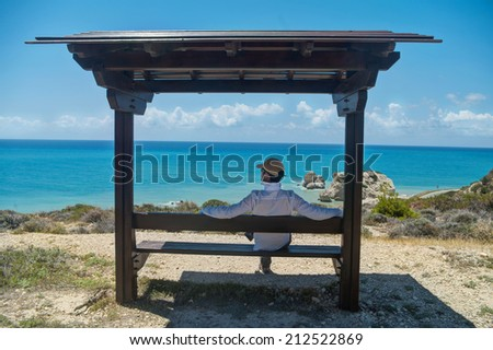 man sitting on bench looking at sea in Cyprus - stock photo