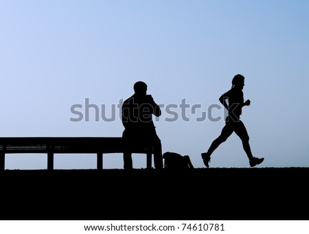 Man sitting on bench watches jogger in dusk silhouette - stock photo