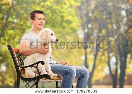 Man sitting on bench with a young dog on blue background - stock photo