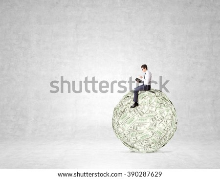 Man sitting on big dollar ball and reading book. Concrete background. Concept of studying business - stock photo