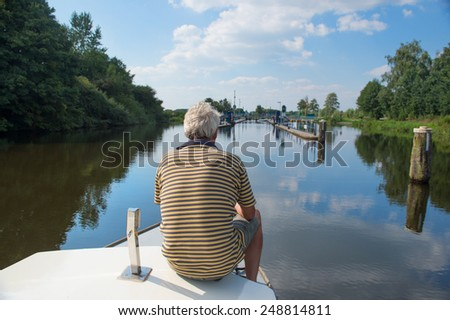 Man sitting on boat near sluice in Holland - stock photo