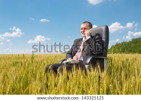 Man sitting on chair and talking on the phone - stock photo