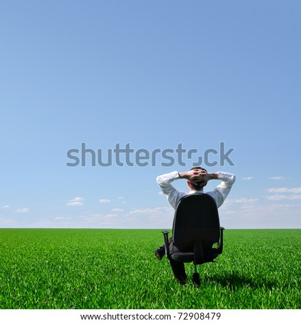 Man sitting on chair on green meadow on blue clear sky background