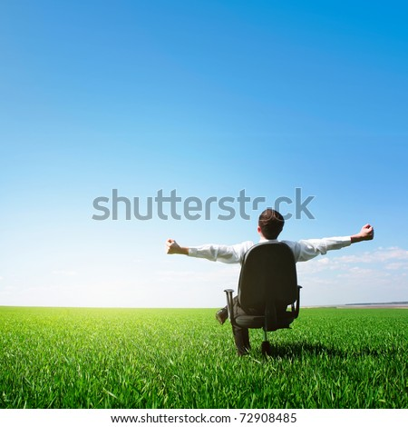 Man sitting on chair on green meadow on blue clear sky background - stock photo