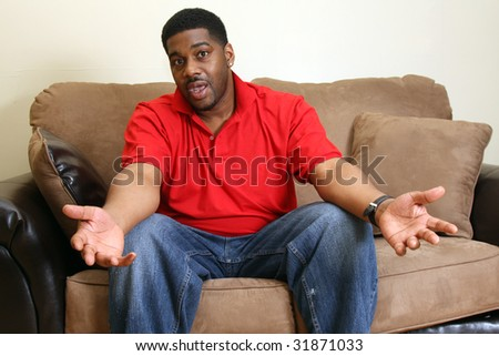 Man sitting on couch in living room - stock photo