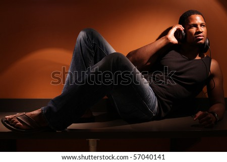 Man sitting on countertop with Headphones on - stock photo