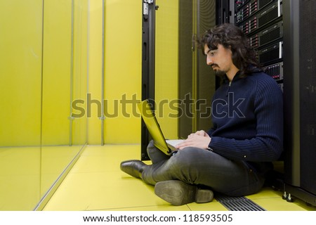 Man sitting on datacenter floor with laptop in front of servers - stock photo