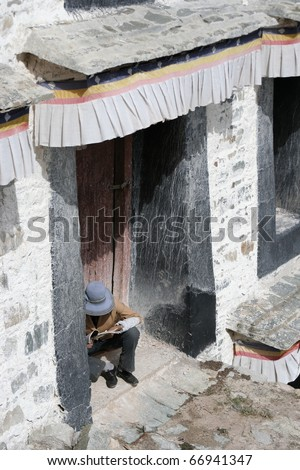man sitting on door step of Potala palace - stock photo