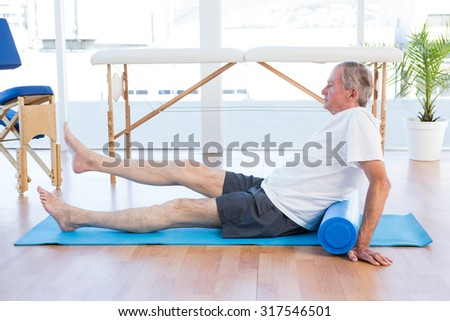 Man sitting on exercise mat in medical office