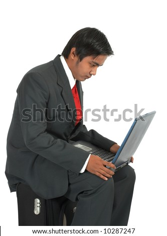 man sitting on his luggage over a white background - stock photo