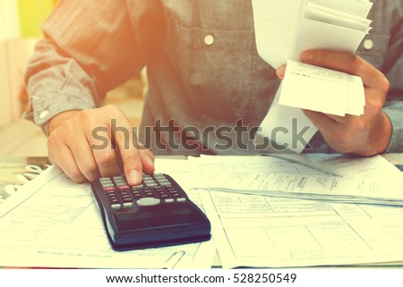 Man sitting on home office using calculator and calculating bills.
