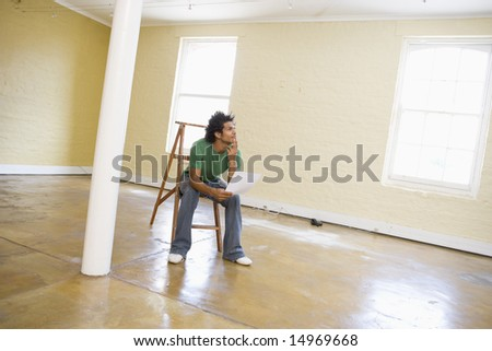Man sitting on ladder in empty space holding paper thinking - stock photo