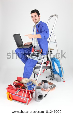 Man sitting on ladder with laptop and plumbing tools - stock photo