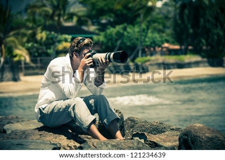 Man sitting on Lava rocks taking pictures in Hawaii - stock photo