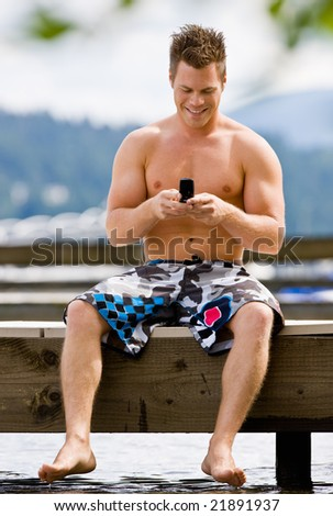 Man sitting on pier text messaging on cell phone - stock photo