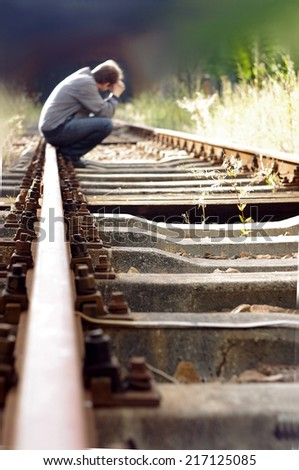 Man sitting on railway track and thinking about suicide. - stock photo