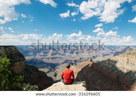 Man sitting on rock overlooking the Grand Canyon National Park on the South Rim whilst on outdoor summer vacation holiday in the US - stock photo