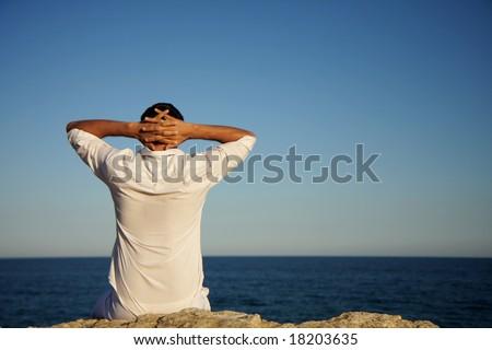 Man sitting on rocks looking and enjoying seaside view - stock photo