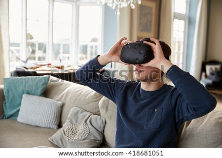 Man Sitting On Sofa At Home Wearing Virtual Reality Headset - stock photo