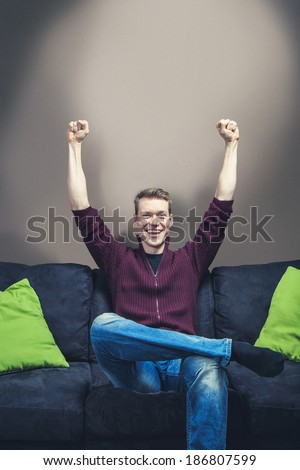 Man sitting on sofa celebrating hands on the air