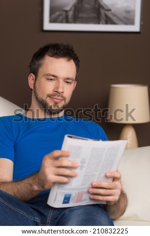 Man sitting on sofa relaxed and reading magazine. cropped image of handsome guy wearing casual clothes. - stock photo
